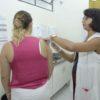 Enfermeira aplica vacina em braço de mulher