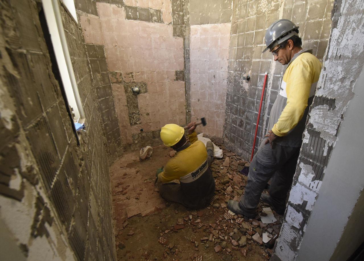 Dois homens em obra de banheiro, removendo pisos e azulejos