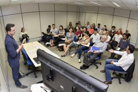 Alunos sentados em cadeiras enquanto professor explica