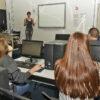 Alunos em frente a computadores olhando para professora