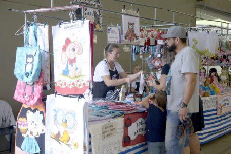 Barraca com comerciante e clientes e artesanato exposto