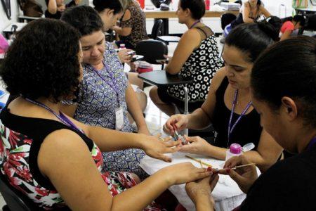 Mulheres fazem as unhas umas das outras em aula