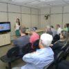Em uma sala de aula, alunos sentados assistem a uma aula; ao centro há uma tela com o conteúdo da aula, tendo um professor ao lado falando aos alunos, e do outro lado uma mulher que observa