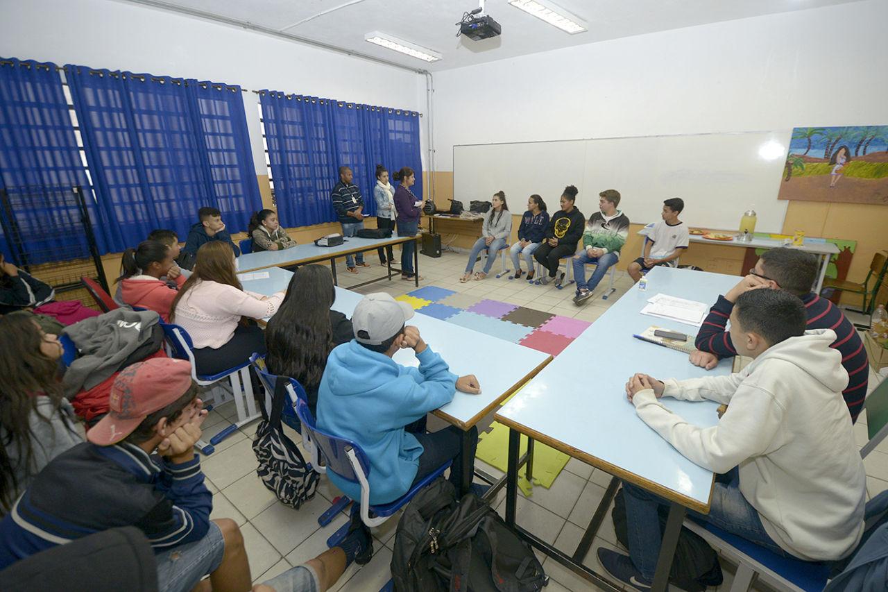 Jovens reunidos em círculo, sentados em carteiros, dentro de uma sala de aula