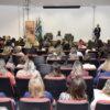 Foto do fundo do auditório, com vagas preenchidas,m e a gestora de Educação sobre o palco