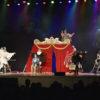 Palco do teatro Polytheama, com plateia não identificável abaixo, com atores fantasiados de pássaros, escadas móveis e uma tenda de circo montada