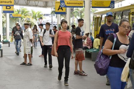 Pessoas caminham por terminal de ônibus