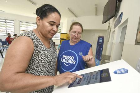 Mulher utiliza totem enquanto é orientada por outra, de uniforme azul com os dizeres 'Posso Ajudar'