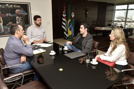Mesa de reunião do prefeito, com o gestor de Cultura e representantes da Associação à mesa, com bandeiras e mesa de trabalho ao fundo