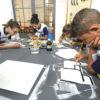 Crianças pintam com pincel placas de madeira, sobre mesa no FAB LAB