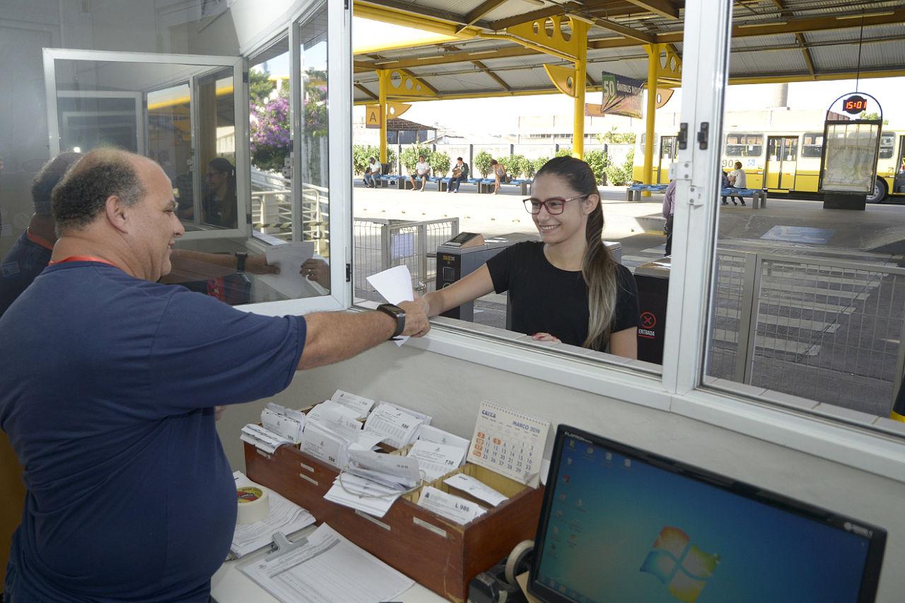 Mulher pega documento entregue por homem, dentro de sala no terminal