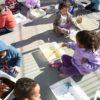 Crianças fazem pinturas sentadas no chão