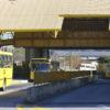 Dois ônibus saem de um terminal, sob um galpão alto