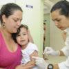Criança com menos de seis anos recebe dose de vacina sentada no colo de mulher