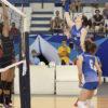 Atleta do time de voleibol feminino em ataque, próximo da rede