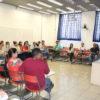 Pessoas sentadas ao redor de sala de aula com palestrante à frente