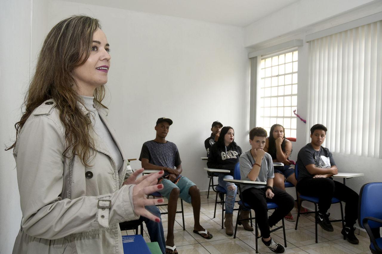 Sala de aula com estudantes e mulher dando explicação, voltada para a direção da lousa da sala