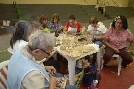 Mulheres sentadas em roda fazem peças com palha