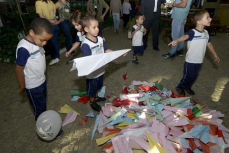 Crianças com uniformes da rede municipal agrupam aviões de papel no térreo do Paço Municipal