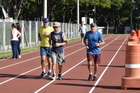 Quatro pessoas correm em pista de atletismo em dia de sol