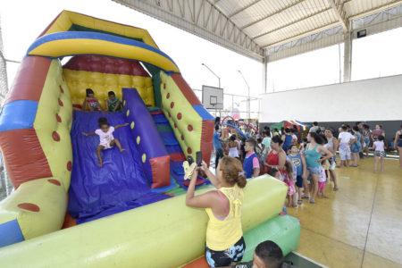 Brinquedo inflável, com crianças pulando e em fila, em quadra coberta