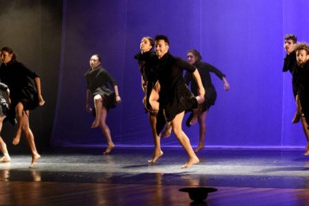 Bailarinos com figurino todo preto, em apresentação no palco do Polytheama, com luzes roxas ao fundo
