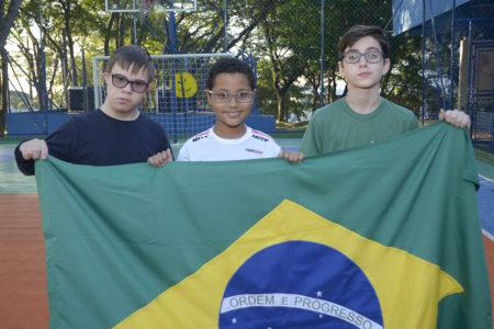 Três crianças seguram bandeira do Brasil