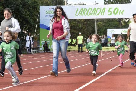 Mulher corre ao lado de criança em pista de atletismo