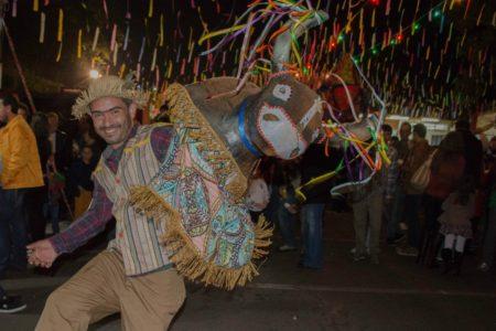 Homem vestido com roupas de festa junina, carregando nas costas boneco de boi, em lugar enfeitado com decoração junina