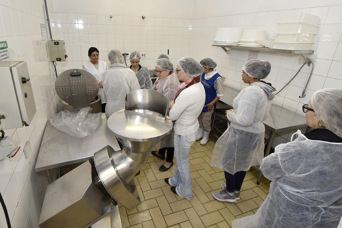 Pessoas com toucas em cozinha industrial