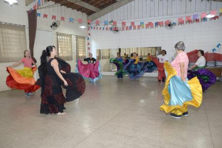Senhoras fazendo coreografias com saias coloridas, em salão com espelho e decoração com bandeiras juninas coloridas
