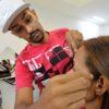 Homem modela a sobrancelha de mulher com linha
