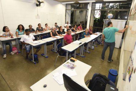 Alunos assistem á aula enquanto professor escreve no quadro
