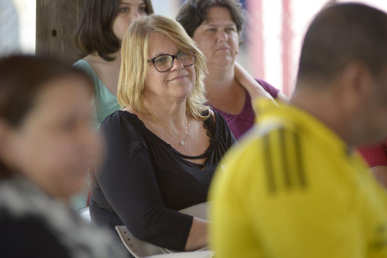 Mulher olha pra frente em meio a outras pessoas sentadas
