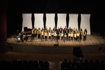 Palco iluminado do teatro Polytheama, com cantores crianças e adultos e pianista, com primeiras filas da plateia à vista