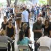 Pessoas são atendidas, em fila, por pessoas sentadas