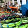 Barraca de feira livre, com legumes e verduras na bandeja, como cenouras, berinjelas e abobrinhas, e cliente ao fundo