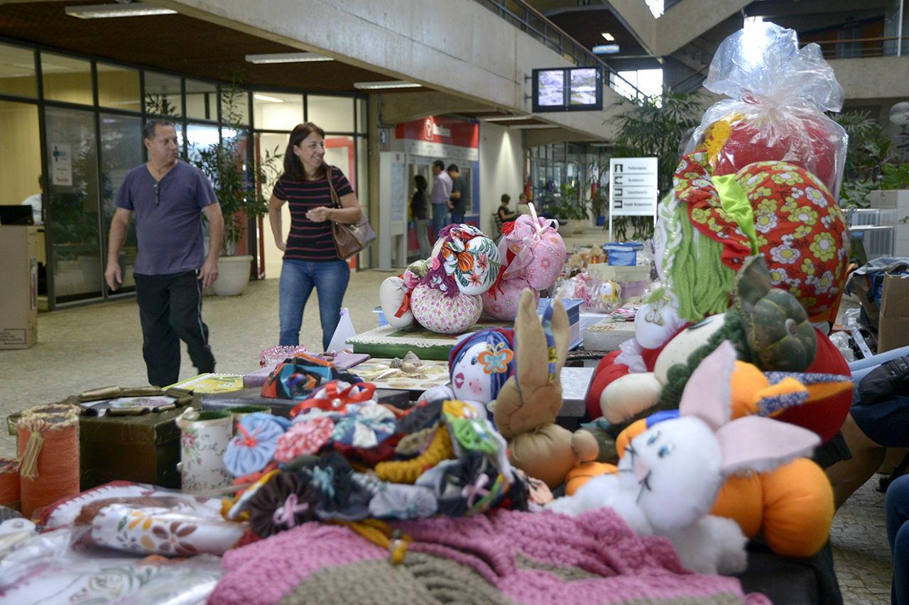 Foto com primeiro plano em bonecas e artesanato de pano colorido e pessoas passando ao lado