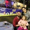 Casal com filha no colo em frente ao Coreto, com decoração junina e banda no palco