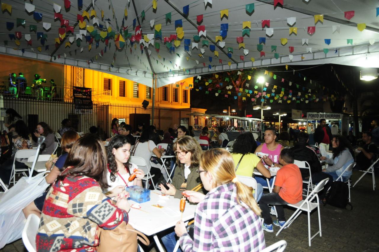 Foto noturna, com pessoas comendo e conversando, sentadas sob uma tenda, com decoração de bandeiras juninas coloridas