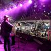 Foto noturna de artistas sobre o palco do coreto, com plateia ao fundo e com decoração junina e show de luzes