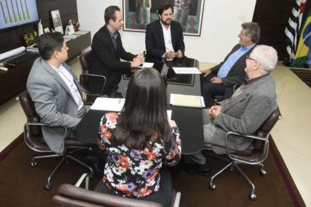 Prefeito, gestores e secretário sentando em volta de uma mesa de reuniões