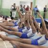 Meninas da ginástica alinhadas em alongamento