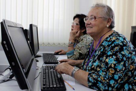 Duas mulheres idosas, em frente a computadores