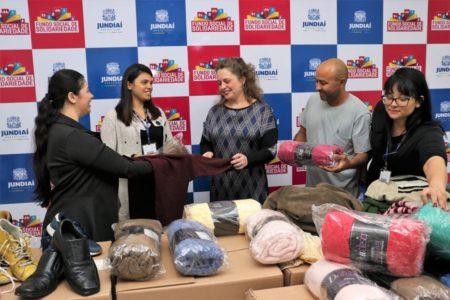 Cinco pessoas seguram blusa de lã e se olham