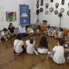 Crianças sentadas em círculo no chão de madeira, com relógios diversos na parede