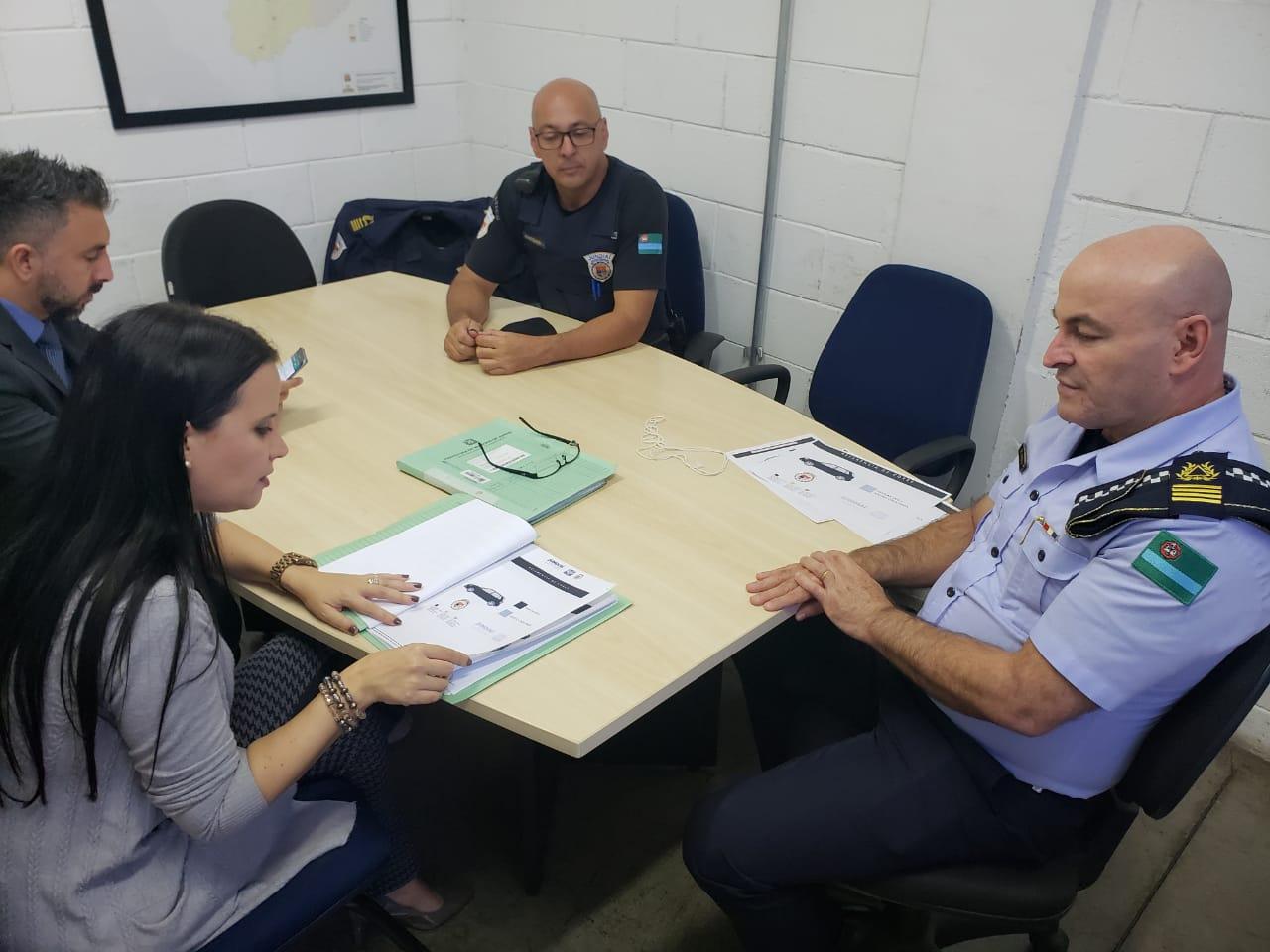 Três pessoas sentadas em mesa de reunião com papéis