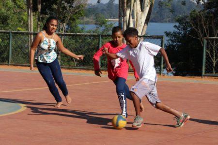 Crianças jogam futebol em quadra