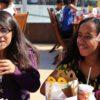 Duas meninas sentadas em mesa com lanches e refrigerantes