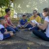 Duas mulheres e três crianças sentadas em círculo no chão